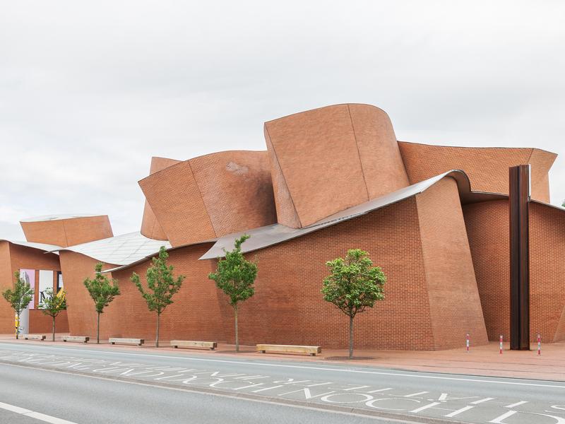 Außenansicht des Museums Marta Herford, auf dem man die geschwungenen Formen des roten Backsteins erkennt. Im Vordergrund ist eine Straße zu erkennen, die am Museum vorbeiführt. Vor den roten Backsteinwänden stehen Bäume mit grüner, runder Baumkrone.